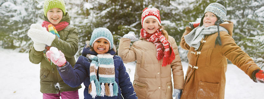Group of children bundled up in the snow with snowballs