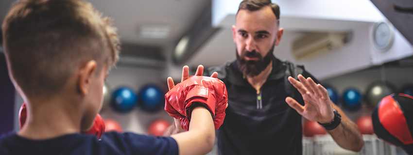 Young boy with boxing gloves strength training with coach