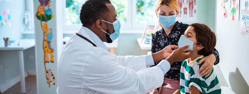 Young boy showing off his muscles with doctor in the background