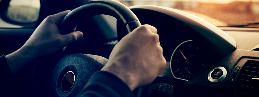 Close up of hands on a car steering wheel