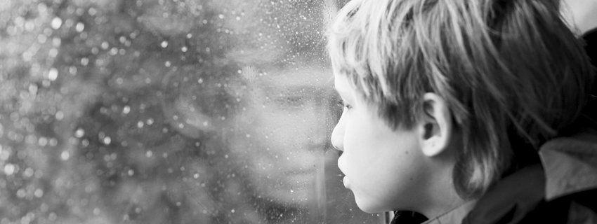 Close up of child looking out a window at the rain in black and white