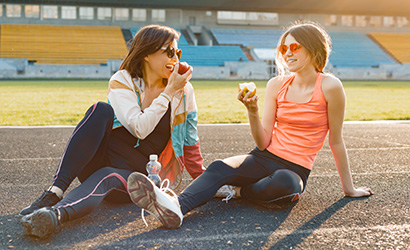 Smiling fitness mother and teen daughter together eating apple sitting on stadium after training on sunny spring day