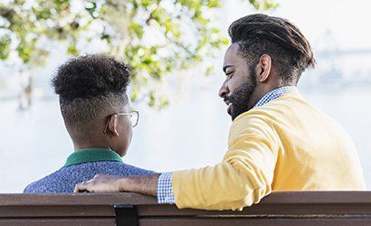 Dad talking to his son on a park bench