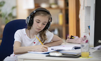 Girl sits at a computer desk at home. She is wearing headphones and writing in her note book.