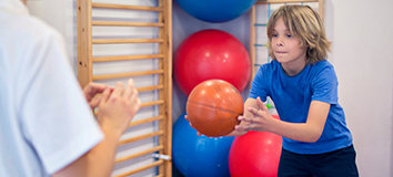 A young boy catches a ball in rehab gym