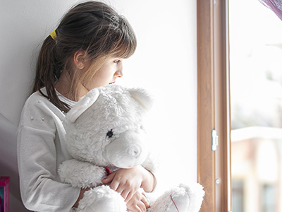 Sad young girl looking out the window with her teddy bear