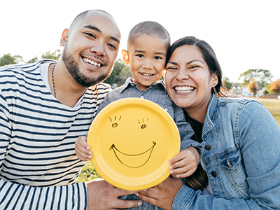 Young family smiling together and holding a happy face paper plate